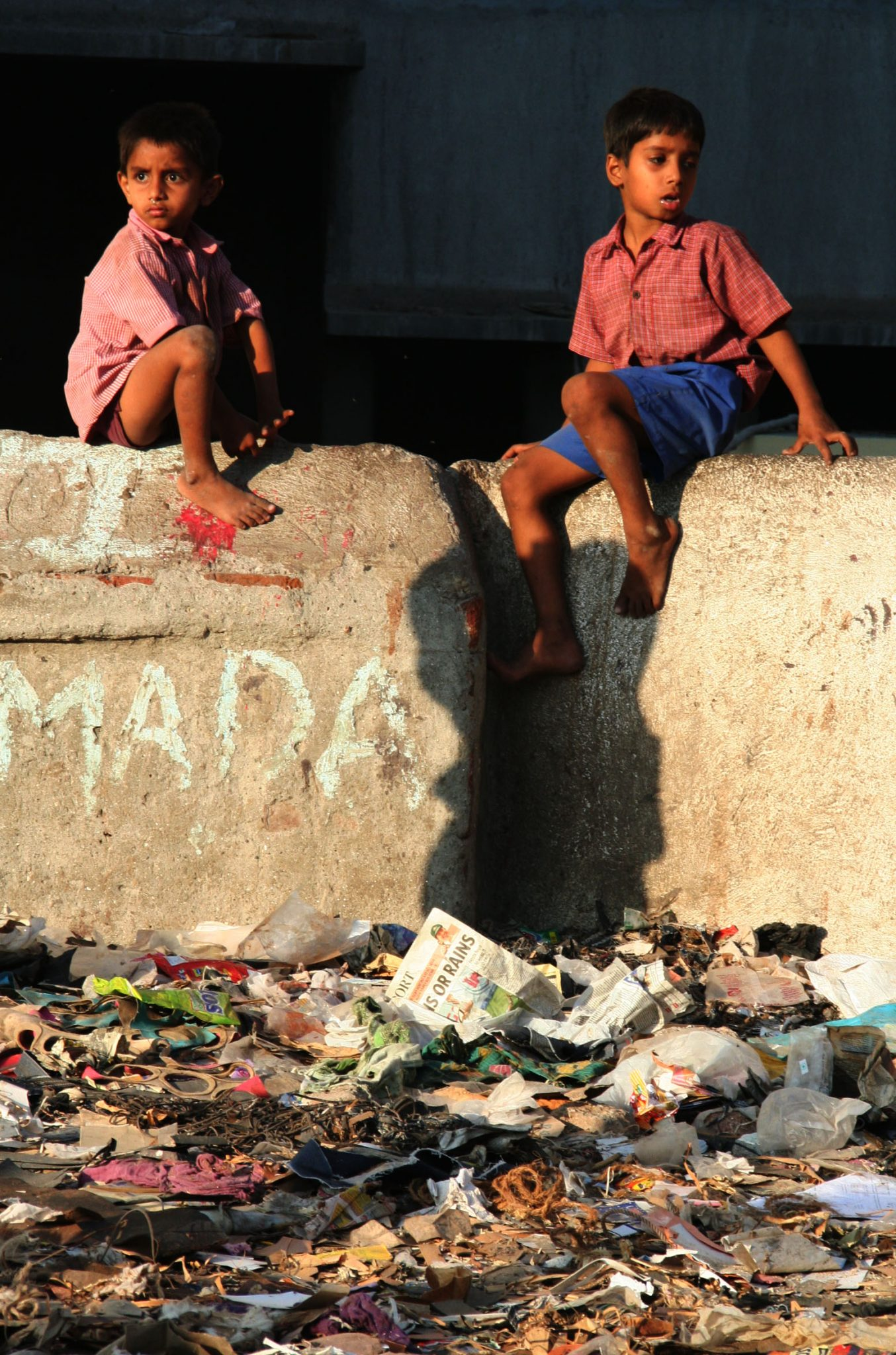 Two boys on a concrete wall, overlooking rubbish in Dharavi.